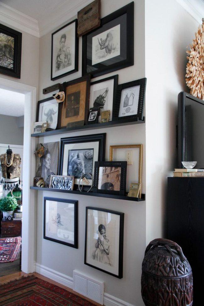 Un couloir éclectique avec des graphismes originaux dans des cadres noirs standard et originaux.  Certaines peintures sont accrochées aux murs, et une partie de la collection est sur les étagères.