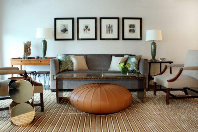 Peintures graphiques dans des cadres noirs sur un mur blanc uni dans le salon