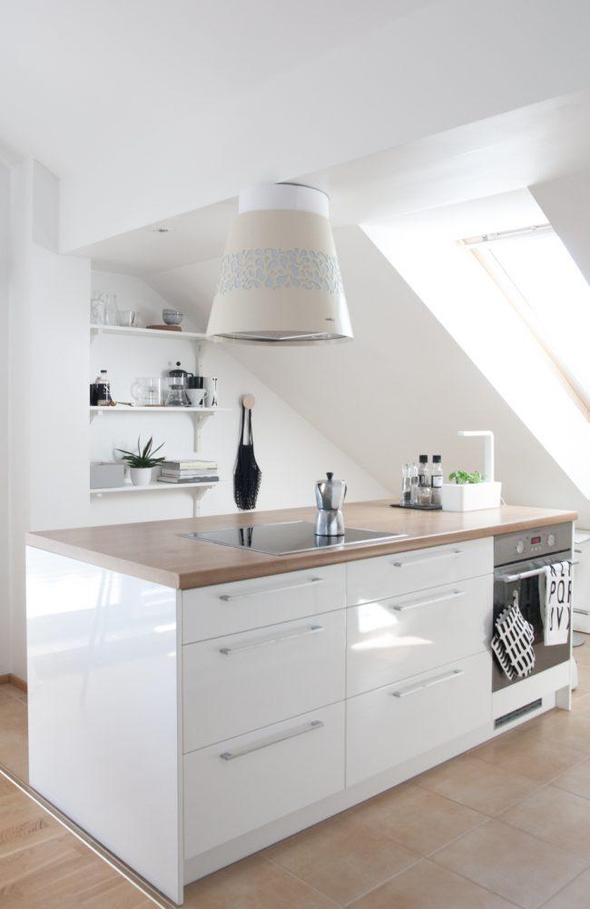 Une petite chambre mansardée est équipée d'une cuisine