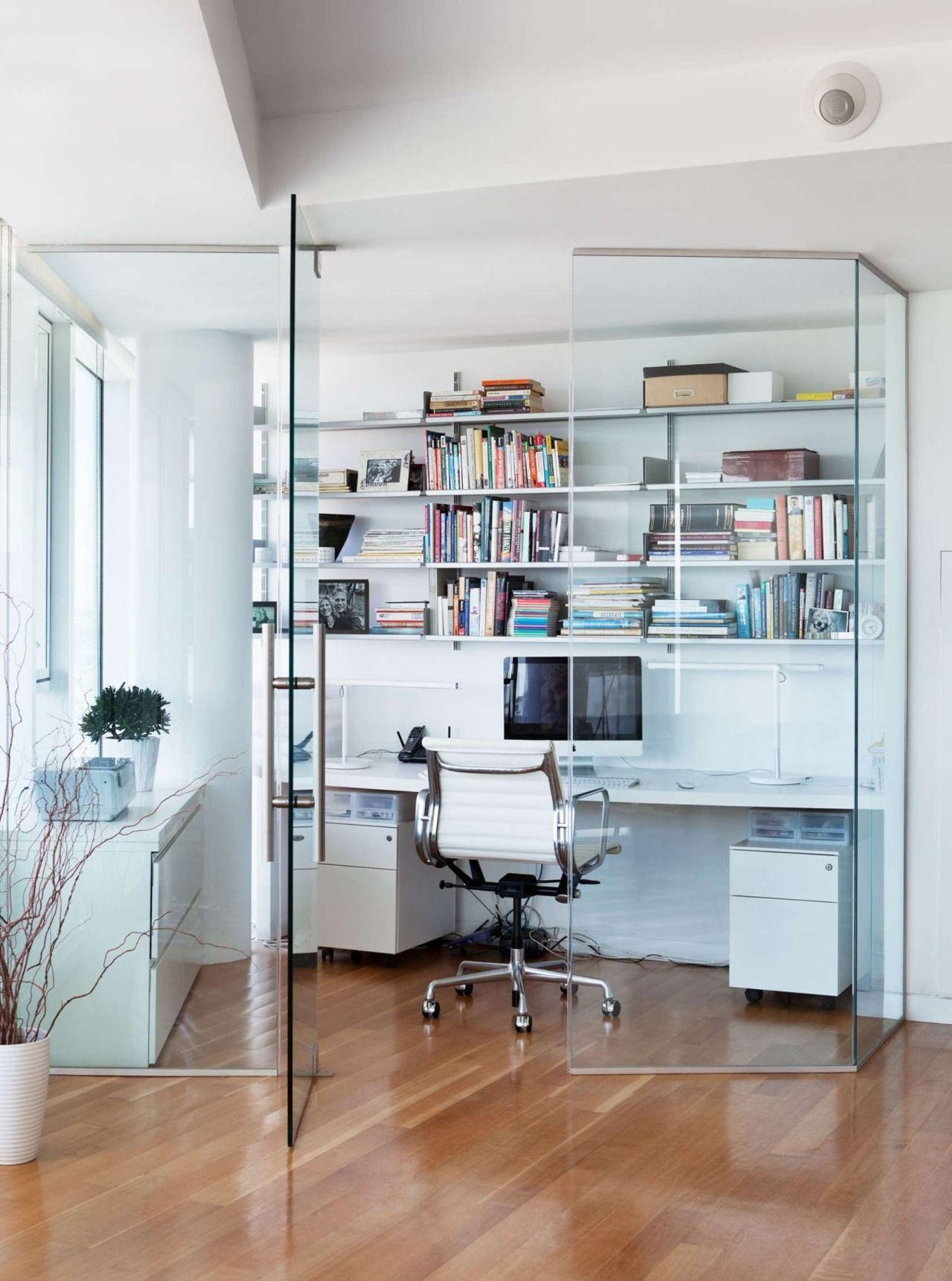 Une cloison en verre transparent définit les limites de l'espace de travail à domicile