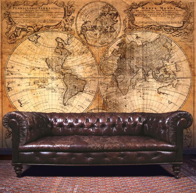 Canapé Chesterfield luxueux sur le fond de l'ancienne carte du monde