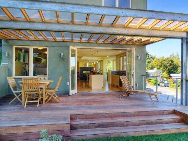 Terrasse avec un toit en polycarbonate à l'entrée de la maison