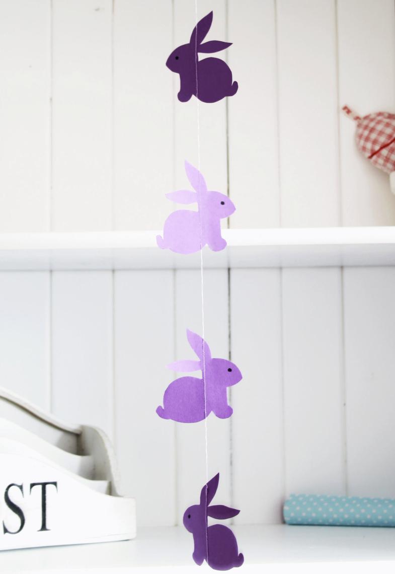 Joyeux lièvres en papier lilas sur une guirlande