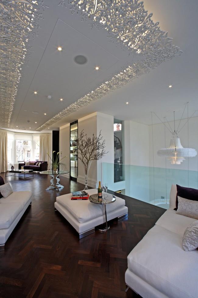 Plafond suspendu créatif à plusieurs niveaux avec éclairage situé derrière une bordure ajourée en stuc de polyuréthane