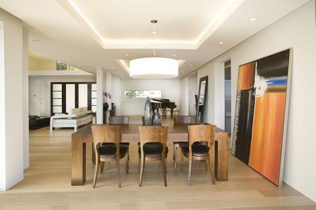 Eclairage central zénithal au dessus de la table à manger et nombreux spots autour de la pièce.  Soit dit en passant, la couleur blanche de la pièce et l'éclairage qui délimite le périmètre de la pièce peuvent la rendre visuellement plus spacieuse.