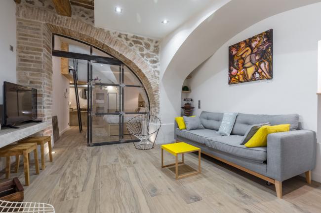 Une combinaison intéressante de construction en plaques de plâtre et de pierre brute dans la décoration intérieure du salon