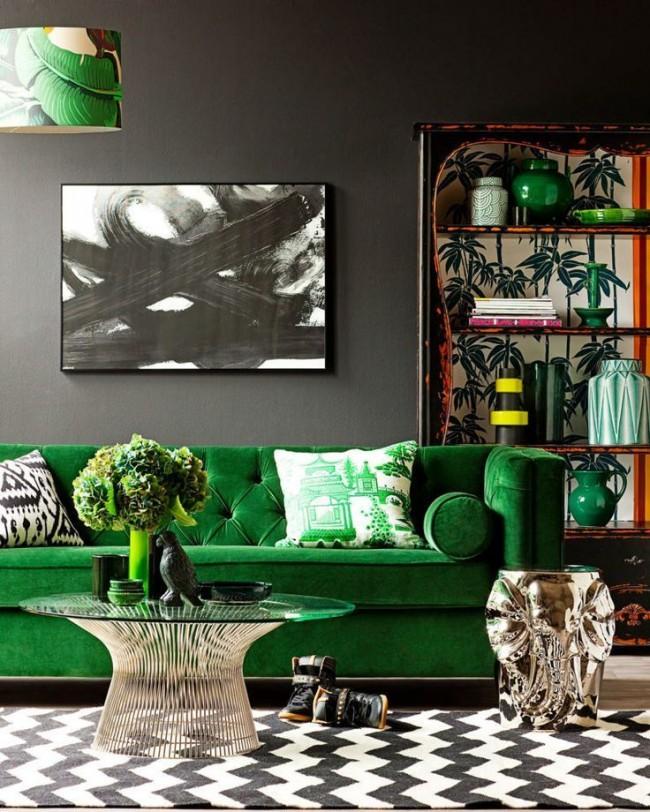 La riche couleur émeraude du meuble dilue la décoration murale noire