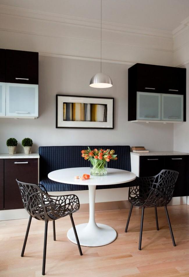 Canapé bleu foncé intégré dans la cuisine avec des chaises intéressantes