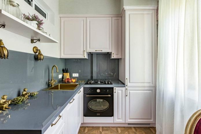 petite cuisine avec des meubles blancs, des plans de travail gris et un tablier du même matériau