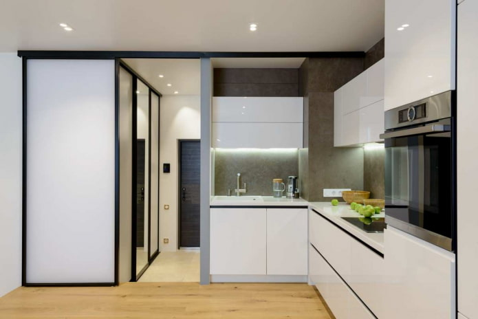 petite cuisine avec des murs gris, du parquet clair et des meubles blancs