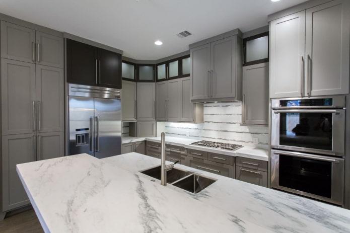 cuisine avec meubles gris clair et comptoirs en pierre blanche