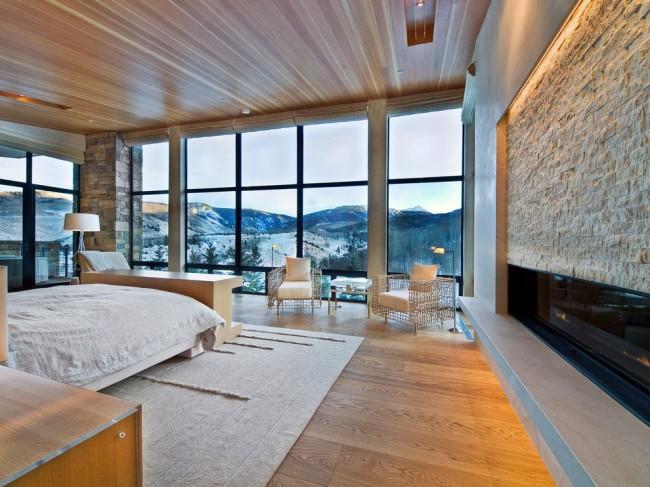 Un mur de verre transparent brouille les frontières entre la pièce et la zone adjacente à la maison
