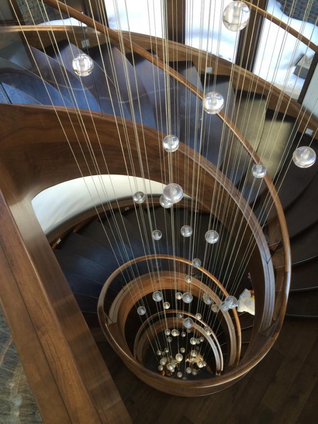 Un escalier en colimaçon en bois peut être agrémenté d'une installation sous forme de fils décoratifs avec des perles suspendues sur toute la hauteur de l'escalier
