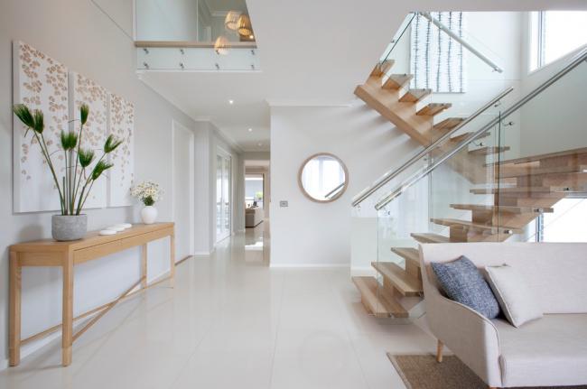 Escalier à deux volées avec marches en bois et garde-corps en verre et métal