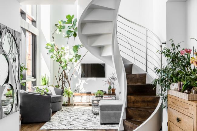 Escalier en colimaçon avec marches en bois dans un intérieur lumineux de style écologique