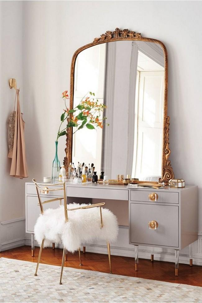 Un immense miroir avec un cadre sculpté et une cape de fourrure sur la chaise rendent le dressing plus élégant