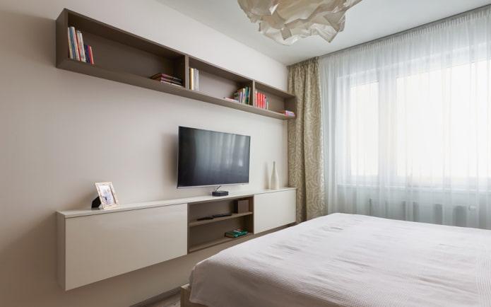 TV sur le mur avec des étagères à l'intérieur de la chambre