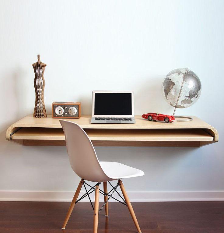 Une table inhabituelle avec un plateau incurvé, avec une surface de retrait supplémentaire pour le clavier, fixée au mur