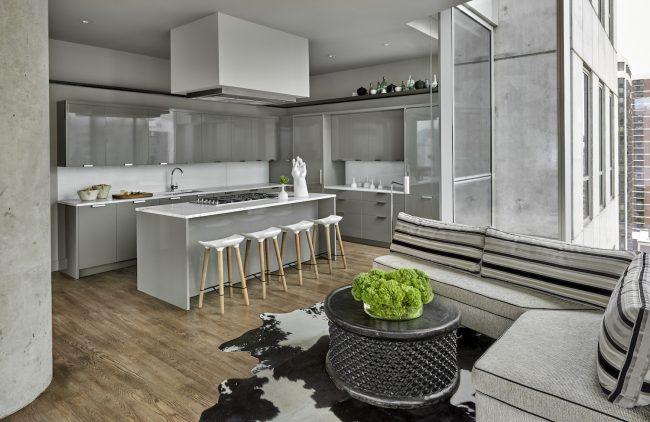 Cuisine-studio esprit loft avec un grand canapé d'angle près de la fenêtre dans l'espace détente