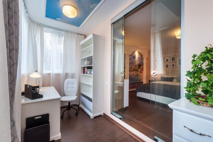 bureau dans la chambre avec une porte coulissante en verre