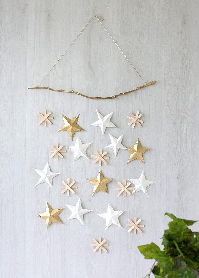 Décoration murale élégante et festive composée d'étoiles en papier de différentes tailles et couleurs