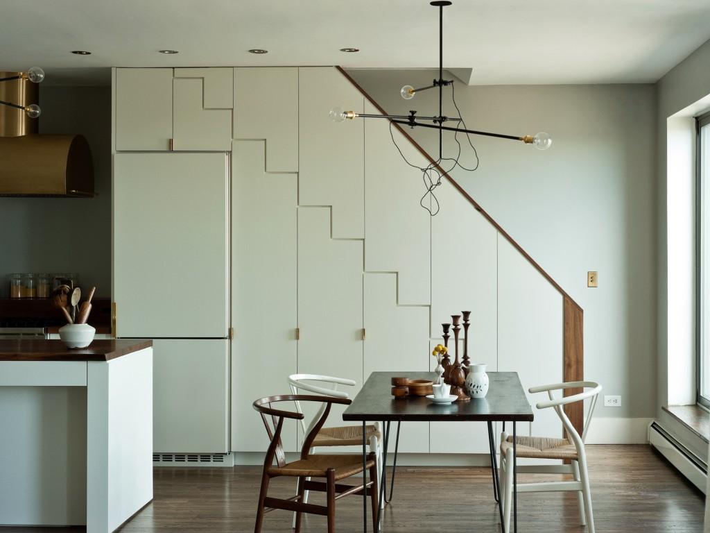 Si vous avez un escalier dans votre maison, il sera alors rationnel d'utiliser l'espace en dessous, par exemple, d'intégrer un réfrigérateur et des armoires de cuisine