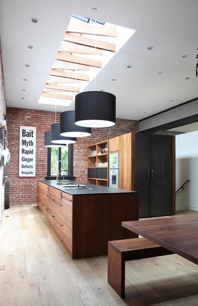 Aménagement non conventionnel du coin cuisine de style loft, où un réfrigérateur est caché au fond des armoires derrière des façades gris foncé