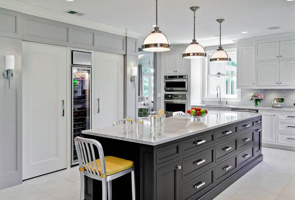 Dans l'espace d'une grande cuisine, un mur séparé a été alloué pour placer l'équipement de réfrigération, le cachant derrière des façades de meubles blancs