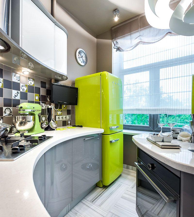 Un réfrigérateur vert vif aux formes arrondies s'intègre parfaitement dans une petite cuisine aux formes bioniques