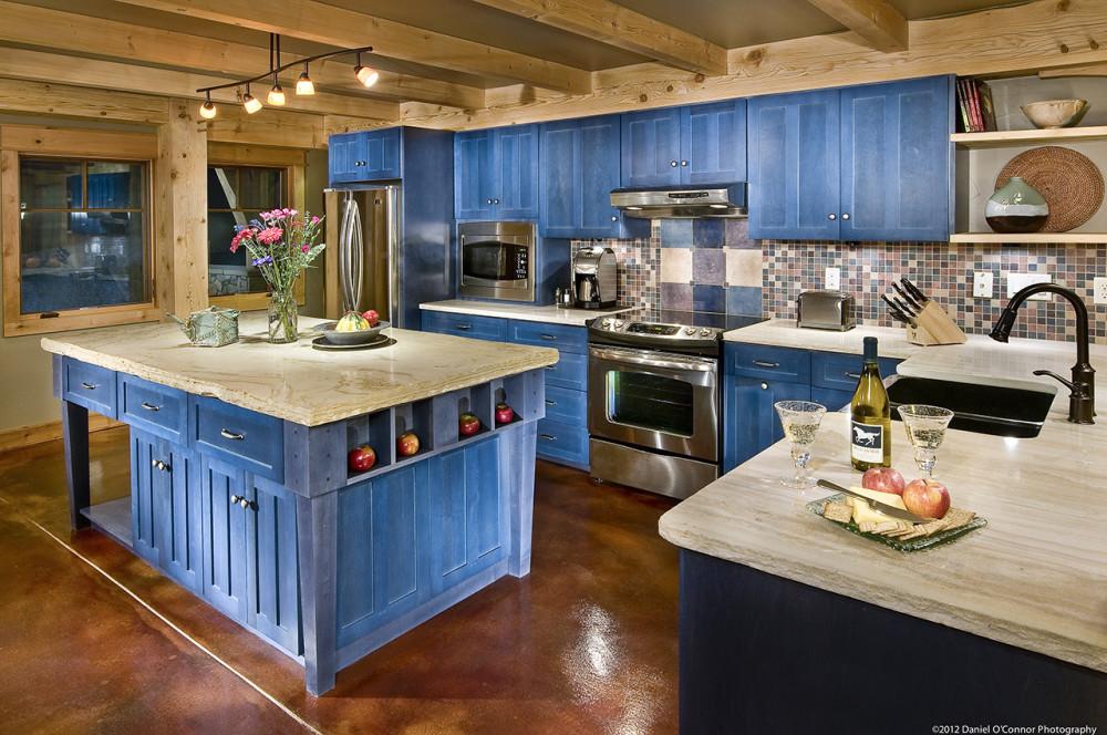 La conception de cuisine en bois avec des façades peintes dans une agréable couleur bleue est une solution inhabituelle.  Le réfrigérateur a pris sa place dans le coin près de la fenêtre