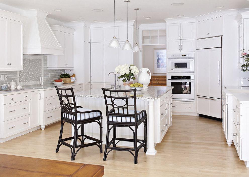Cuisine blanche spacieuse avec un réfrigérateur intégré dans le coin