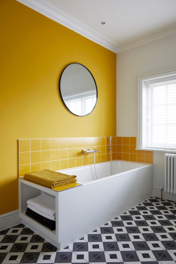 salle de bain avec mur jaune et sol en mosaïque noir et blanc
