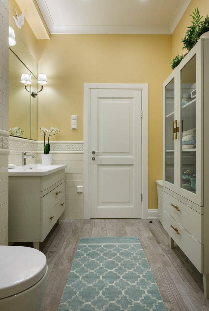 salle de bain aux murs jaune pâle et aux meubles blancs