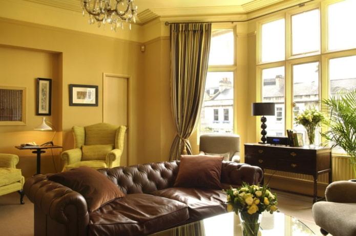 salon jaune foncé avec canapé en cuir marron