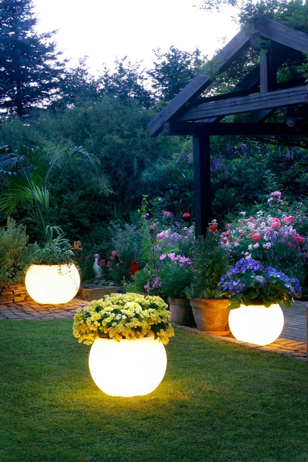 Les pots de fleurs brillants dans le noir sont une idée très fonctionnelle, car la nuit ils jouent le rôle de lanternes et le jour ce sont des pots de fleurs ordinaires avec des fleurs.