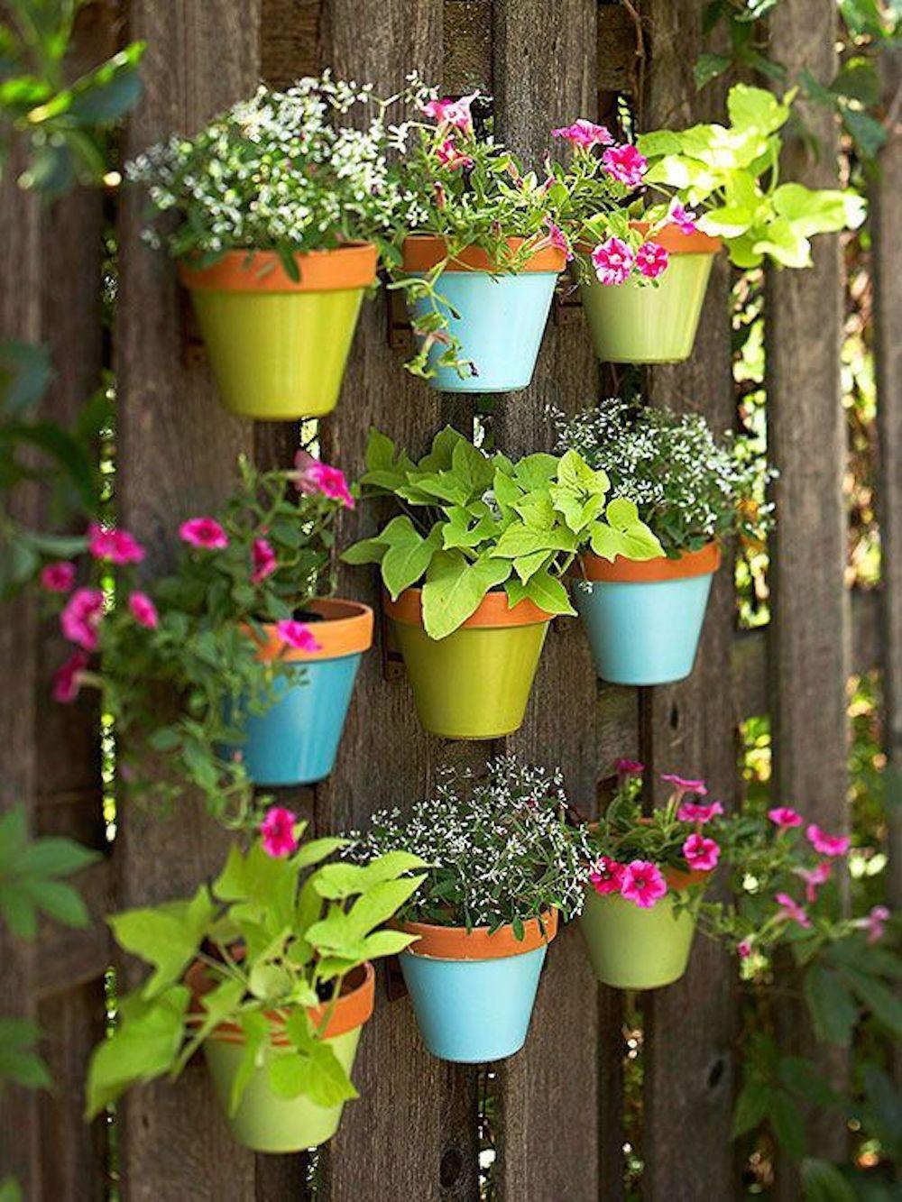 De petits pots en plastique avec des fleurs décoreront la clôture à la campagne