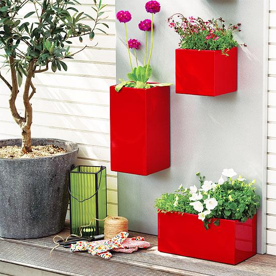 Une composition lumineuse avec trois pots de fleurs rouges avec des fleurs décorera un coin repos