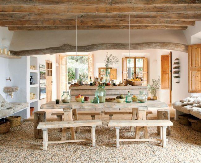Cuisine-séjour dans une maison de campagne : sol en pierre, plafond en bois, mobilier en matériaux naturels