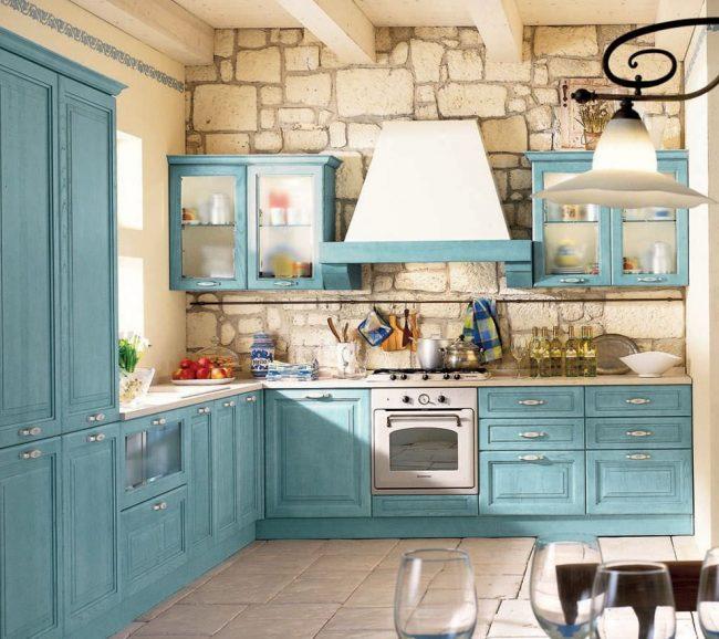 Cuisine de style provençal rustique : décoration murale en pierre claire, ensemble de cuisine bleu en bois naturel