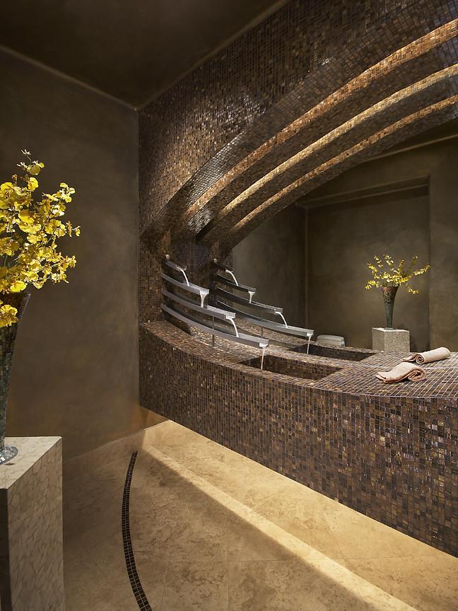 Intérieur de salle de bain élégant avec mosaïques : robinet cascade unique et lignes fluides sculptées de surfaces en mosaïque