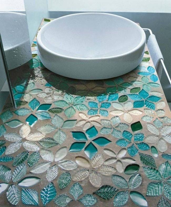 Une création unique : une mosaïque de verre et d'autres matériaux pressés dans un plan de travail en béton