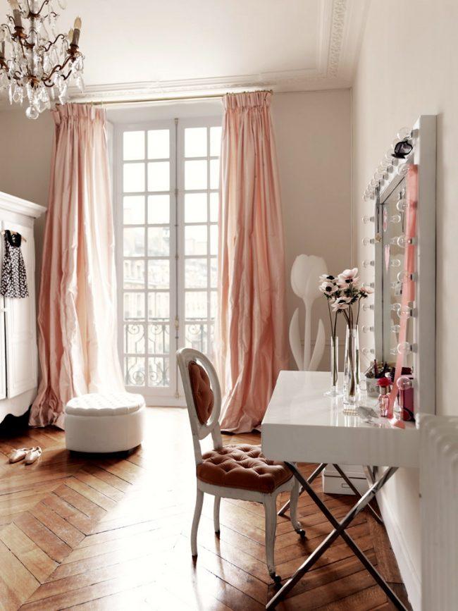 Beau miroir dans un cadre blanc avec une coiffeuse et un éclairage dans la chambre des enfants