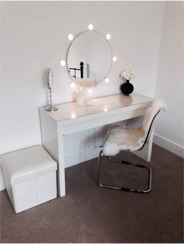 Petit miroir rond avec éclairage installé séparément et petite coiffeuse dans le style du minimalisme