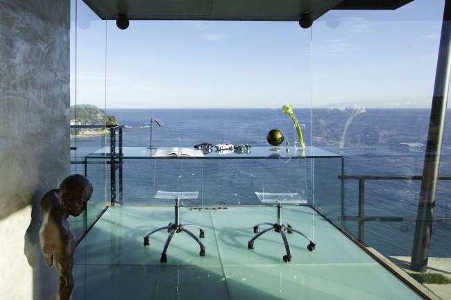 Des murs de verre et du verre, des meubles en apesanteur dans un superbe bureau à domicile avec vue sur la mer.  Aucun décor n'est simplement nécessaire ici.