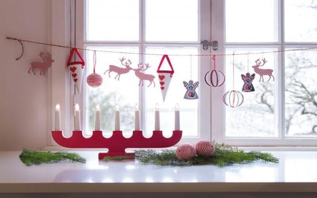 Un chandelier rouge et des éléments de jouets suspendus dilueront le rebord de la fenêtre blanc comme neige