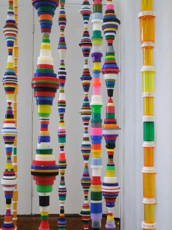 Artisanat à partir de bouchons de bouteilles en plastique.  Les couvercles fixés verticalement de différentes tailles font des décorations suspendues inhabituelles