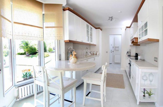 Le manque de lumière naturelle dans la cuisine-couloir peut être un problème : installez des fenêtres panoramiques dans la salle à manger et choisissez un ensemble de cuisine lumineux pour résoudre le problème