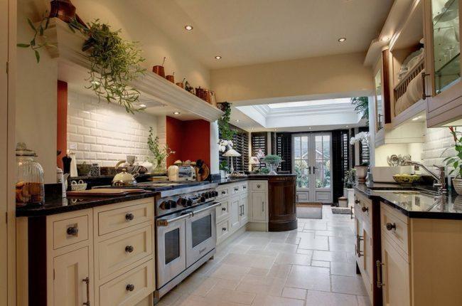 Grande cuisine dans le couloir d'une maison de campagne avec four et lave-vaisselle