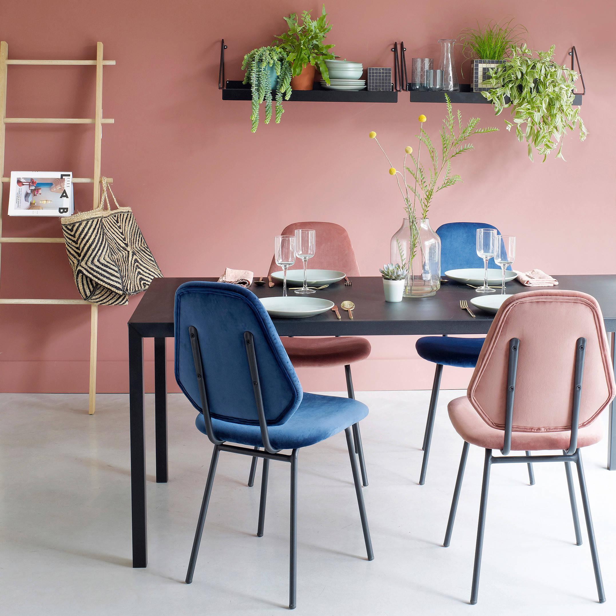 Une table en plastique noir contraste dans une entreprise avec des chaises colorées