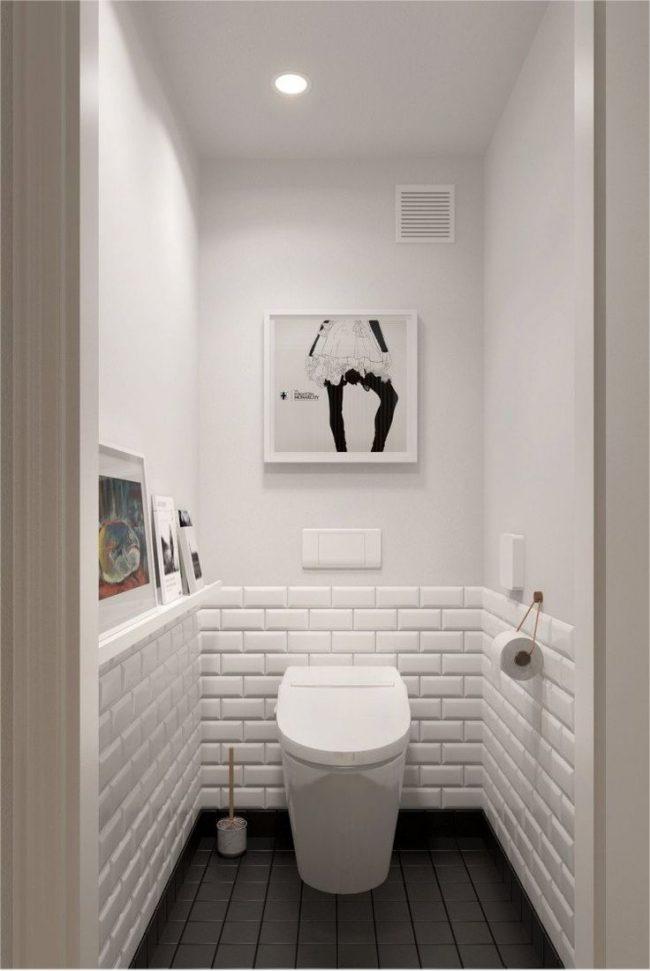 Les toilettes aux couleurs claires et au sol contrasté semblent visuellement plus larges